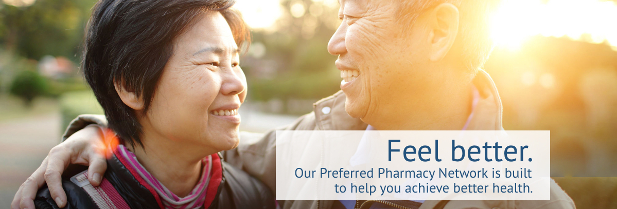 Older Asian couple smiling at each other after discussing Sun Life Preferred Pharmacy Network
