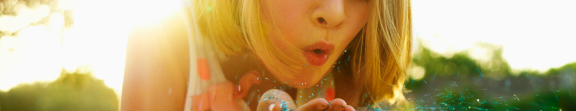 Young girl blowing glitter from cupped hands